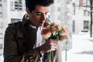 young man holding flowers